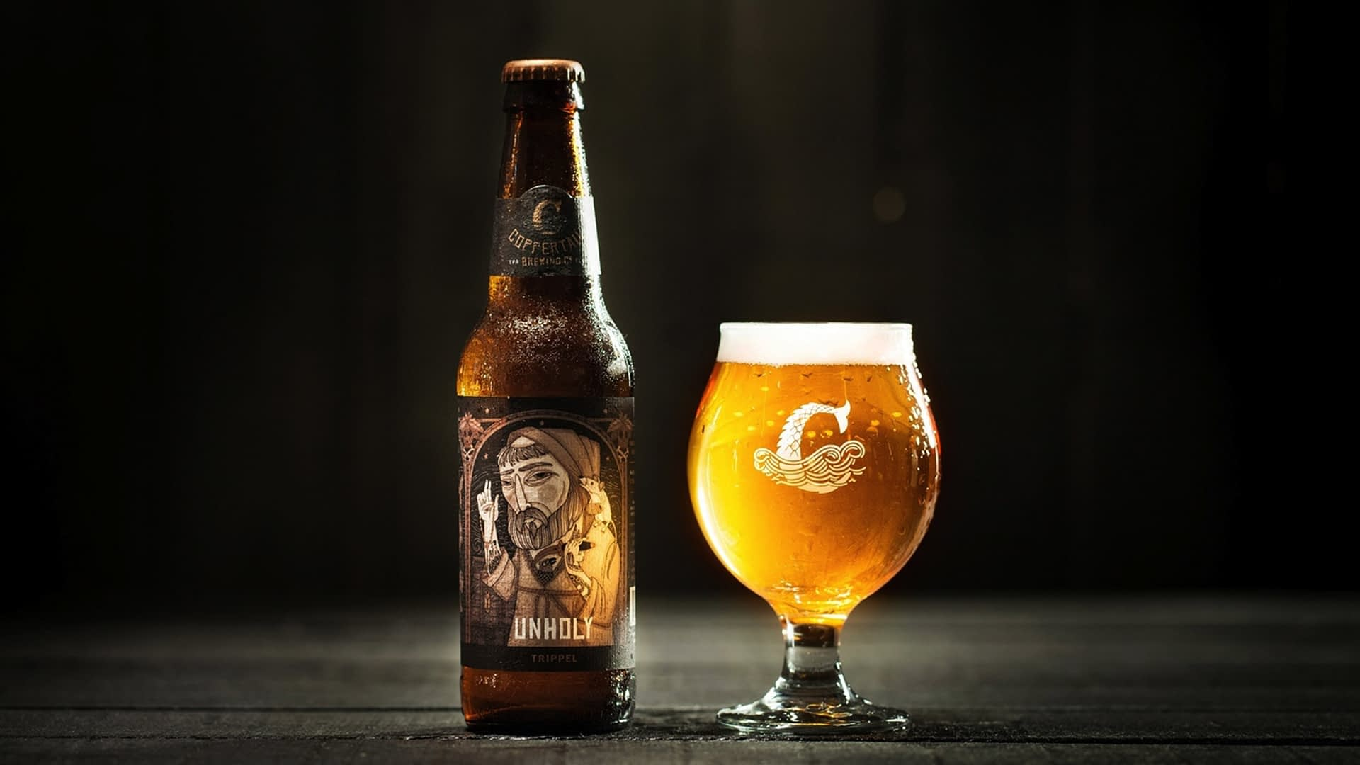 A bottle and a glass of Coppertail's Trippel Unholy beer.