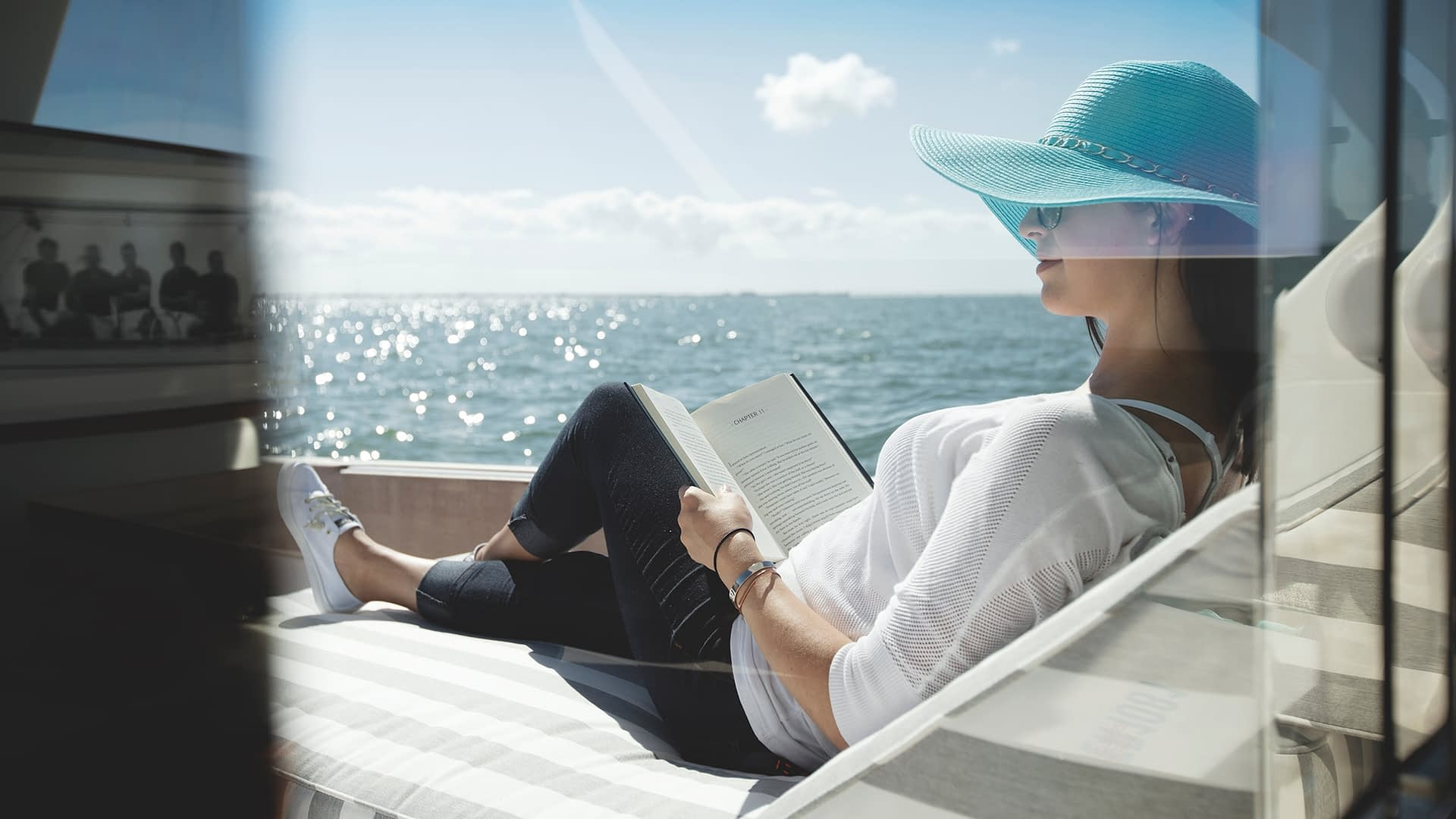 Woman relaxing in hat on back of boat in water
