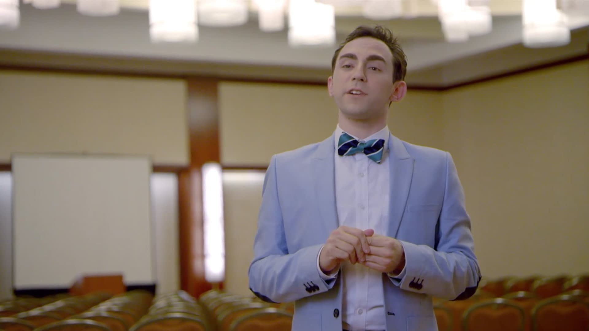 Man in empty auditorium in a blue suit and bowtie.