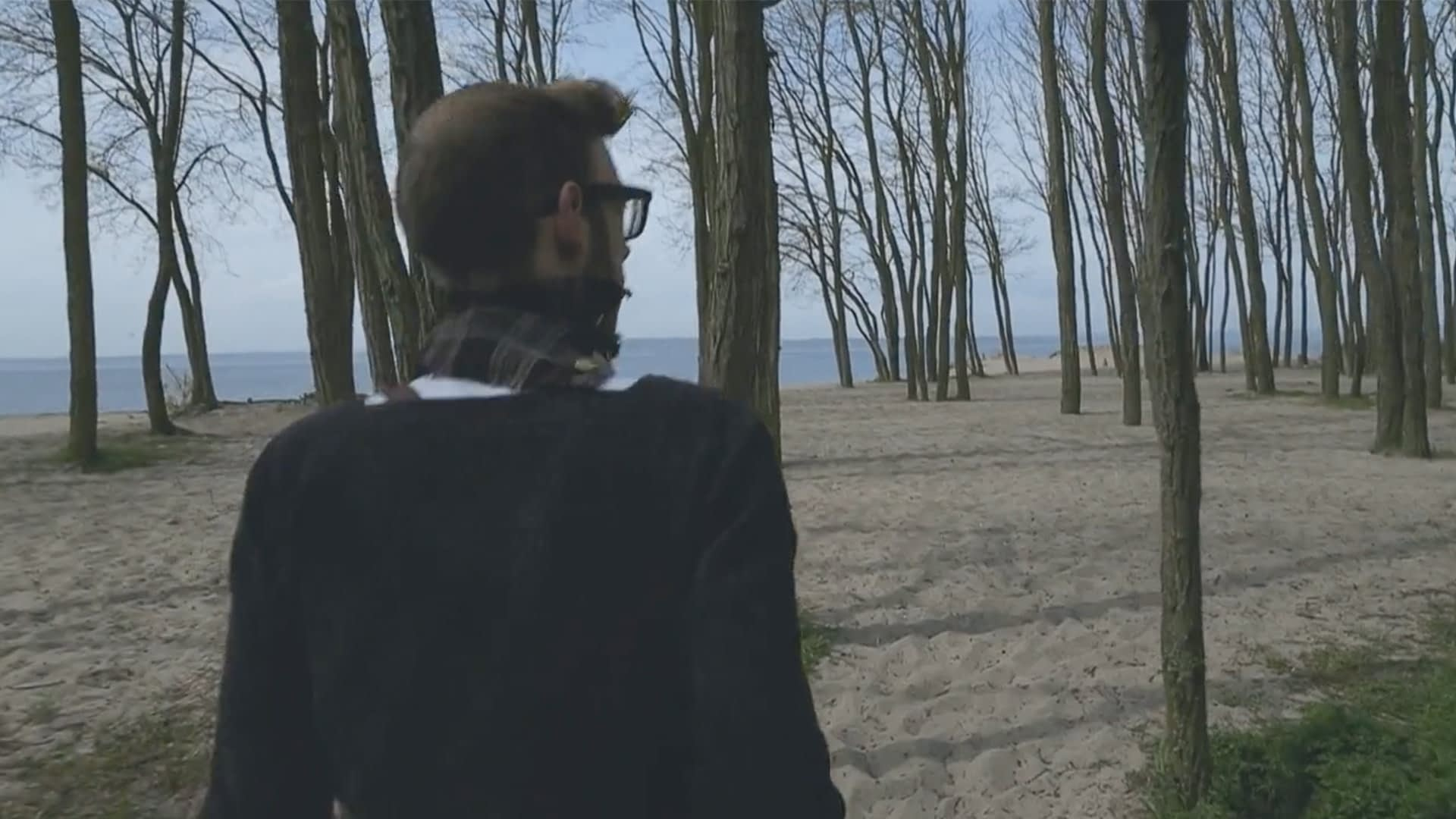 Man with a scarf and sweater is walking through a forest of bear trees near the beach.