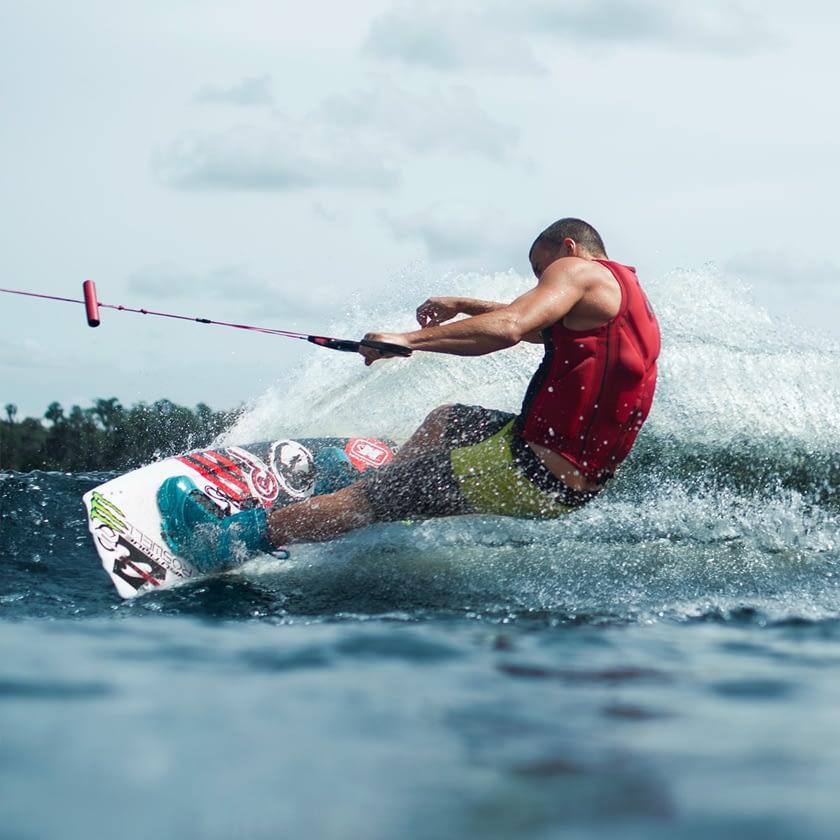 Muscular man wake boarding.