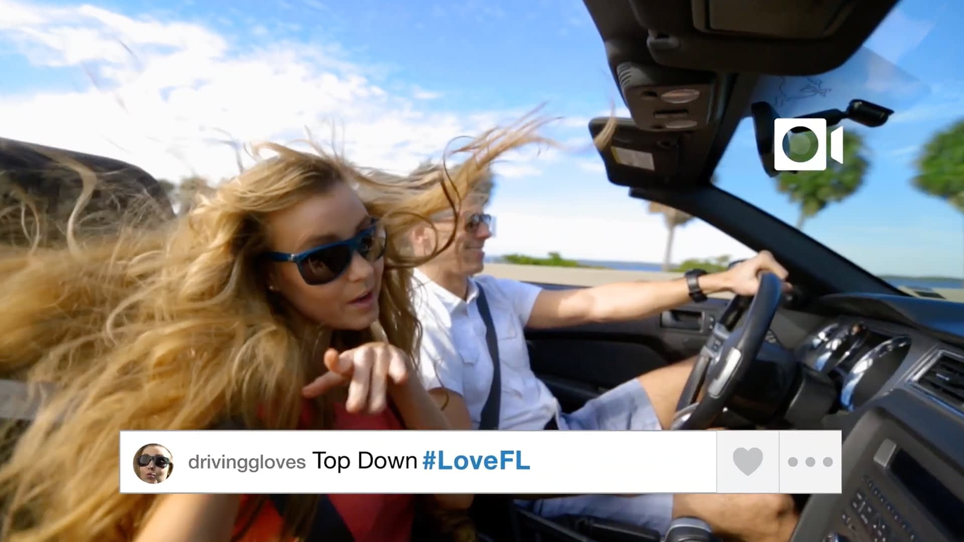 A screen grab of a woman's instagram post. She is the passenger in a top down convertible with her hair flying everywhere. The post says Top Down #LoveFL.
