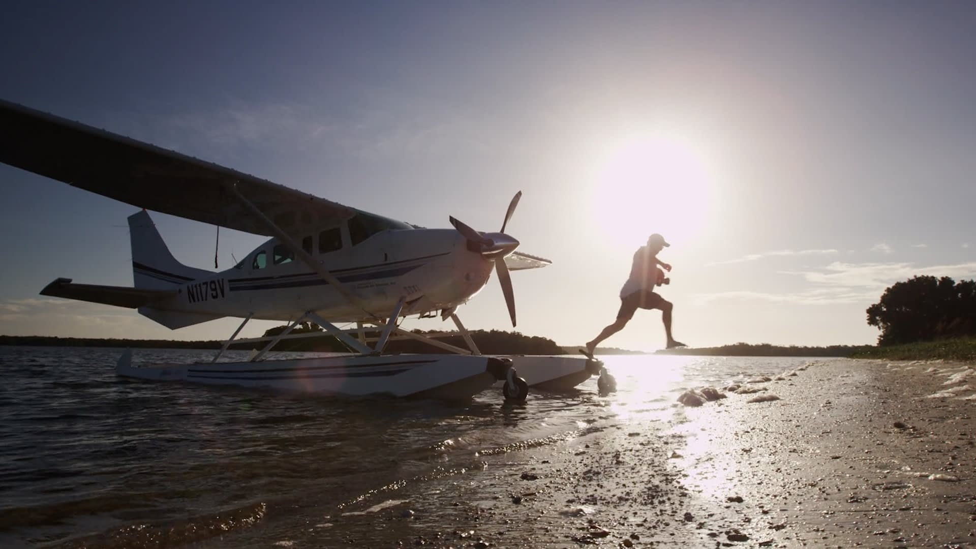 A man jumping onto the beach from a parked seaplane.