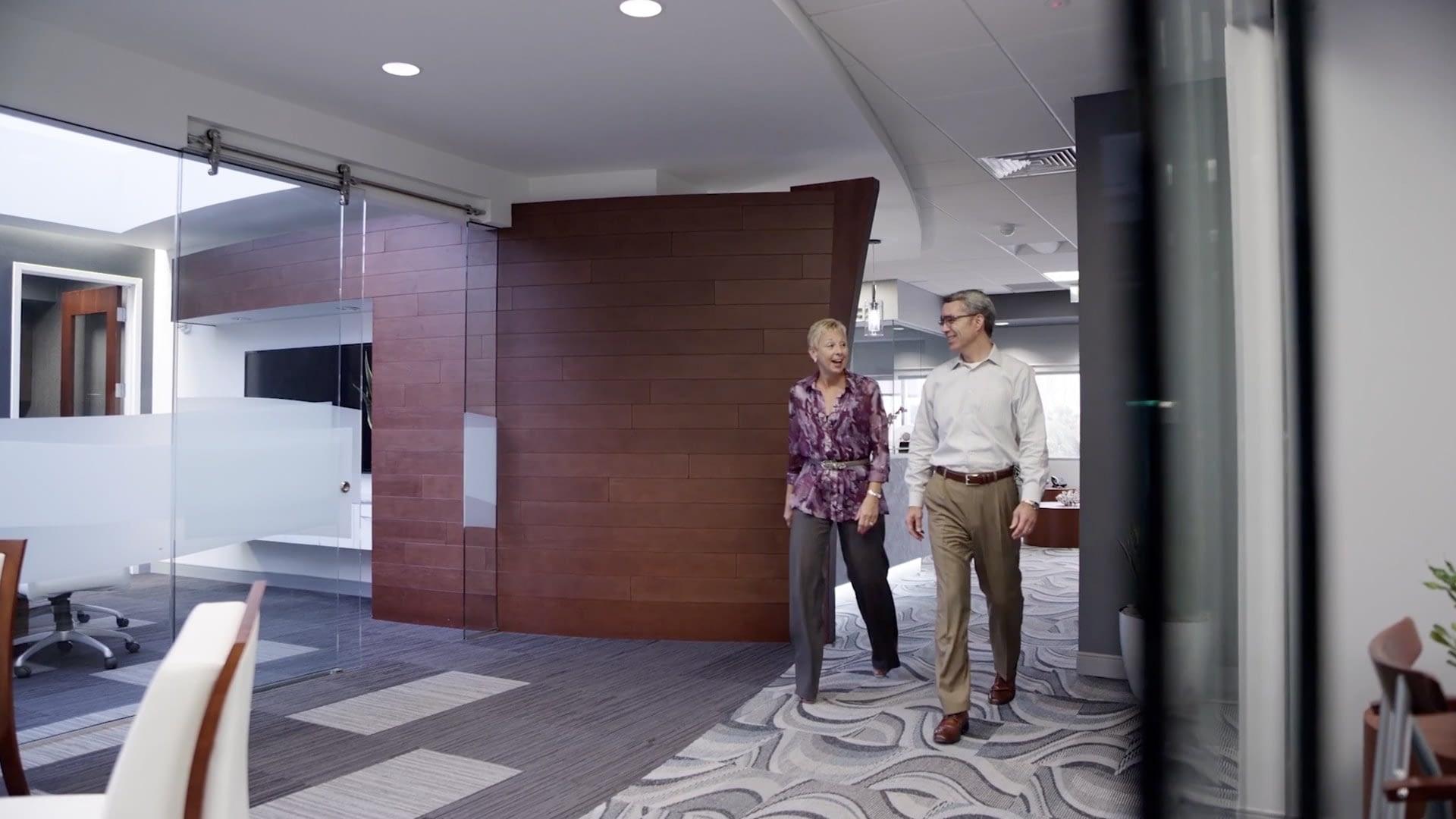 Two people walk down corridor
