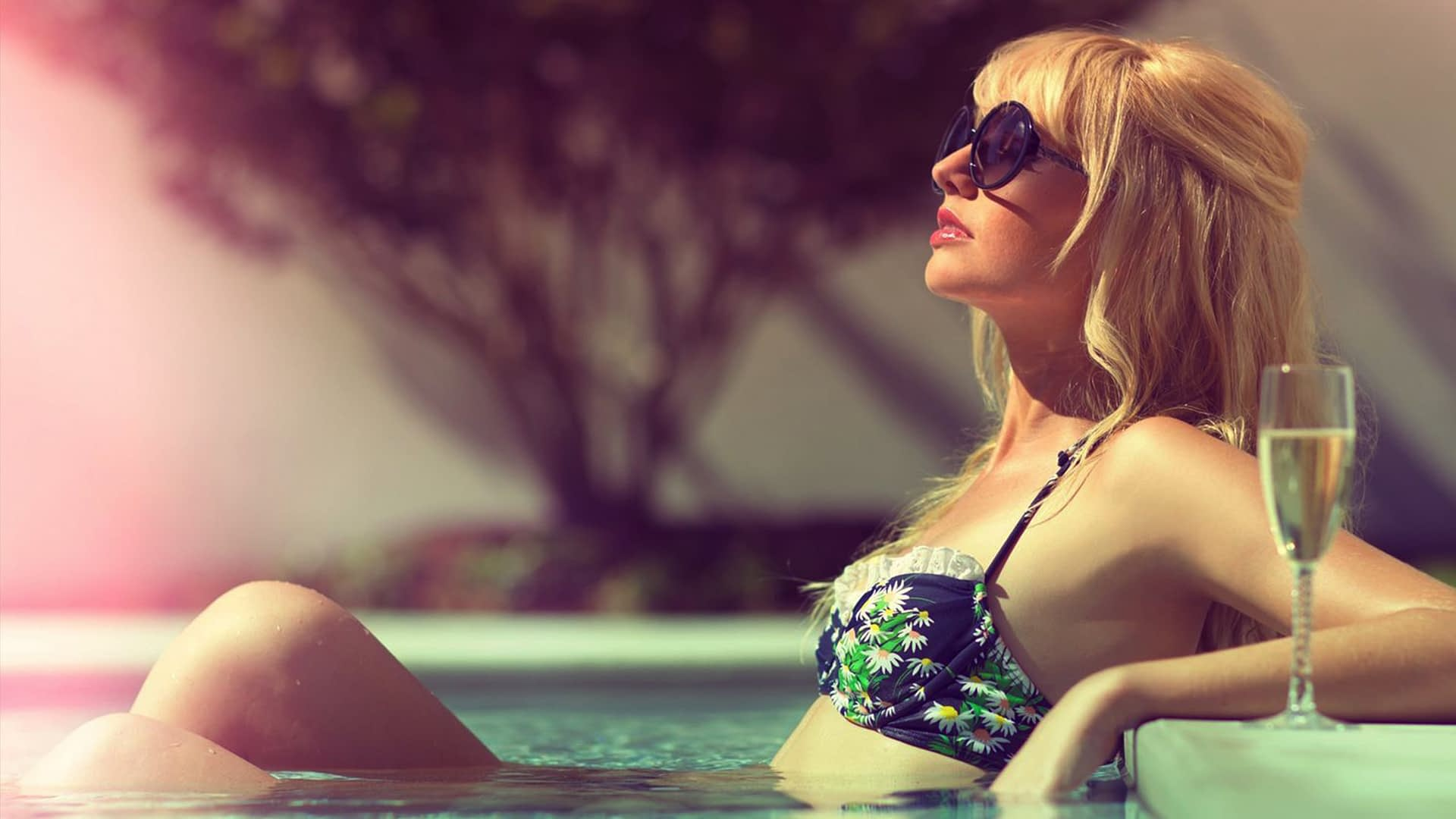 A woman in retro-looking bathing suit and sunglasses laying at the edge of Epicurean Hotel's pool with a glass of wine.