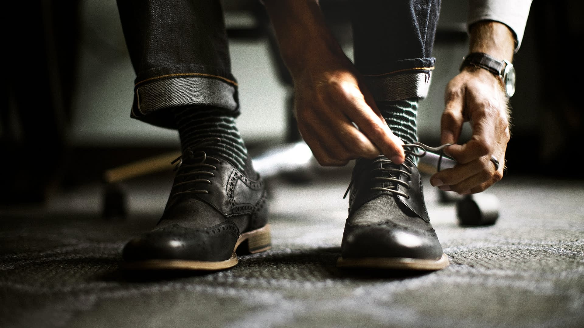 Man ties shoes at luxury hotel in Seattle, Washington.