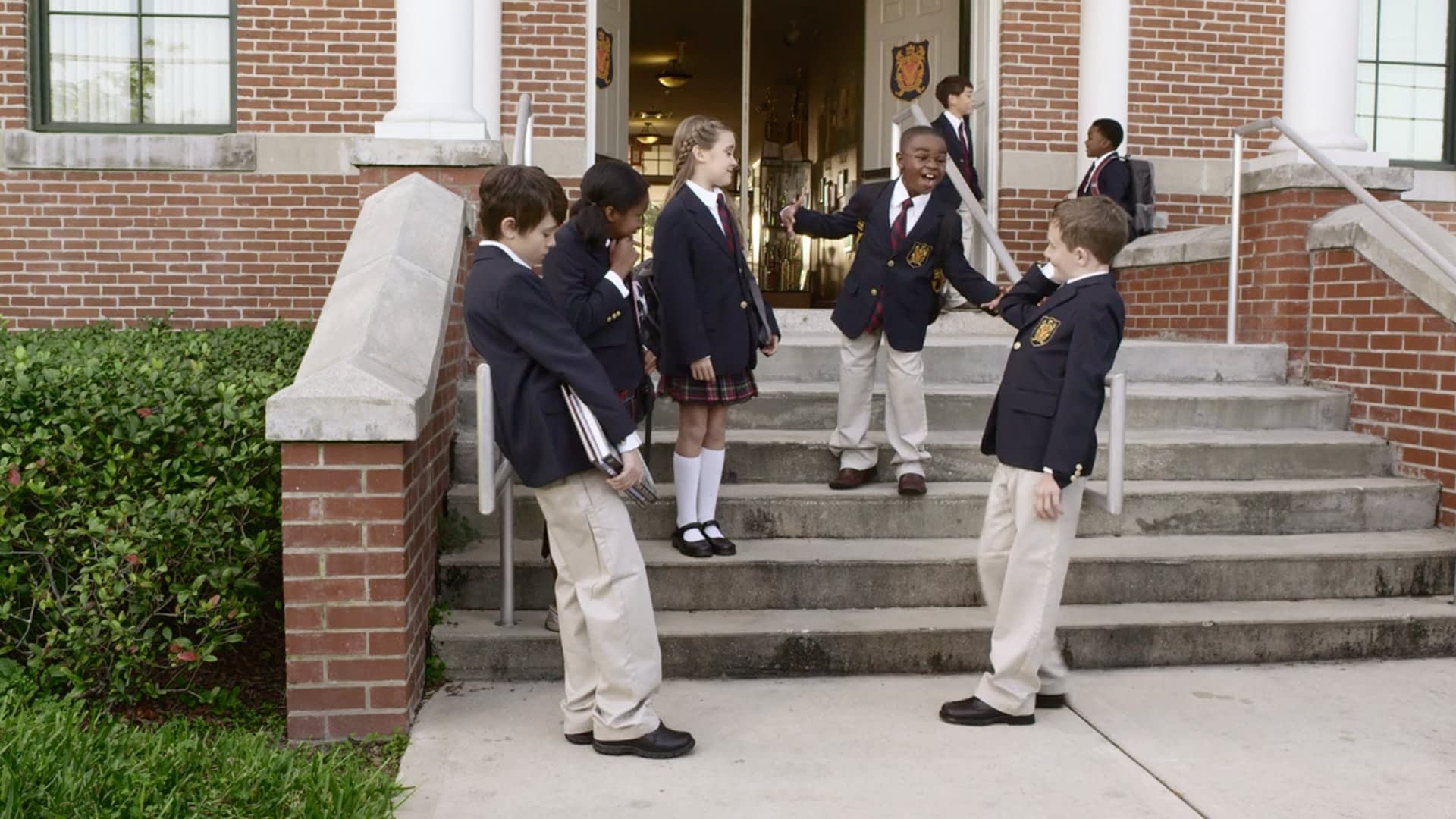 Six children standing on the steps of their school in uniform.