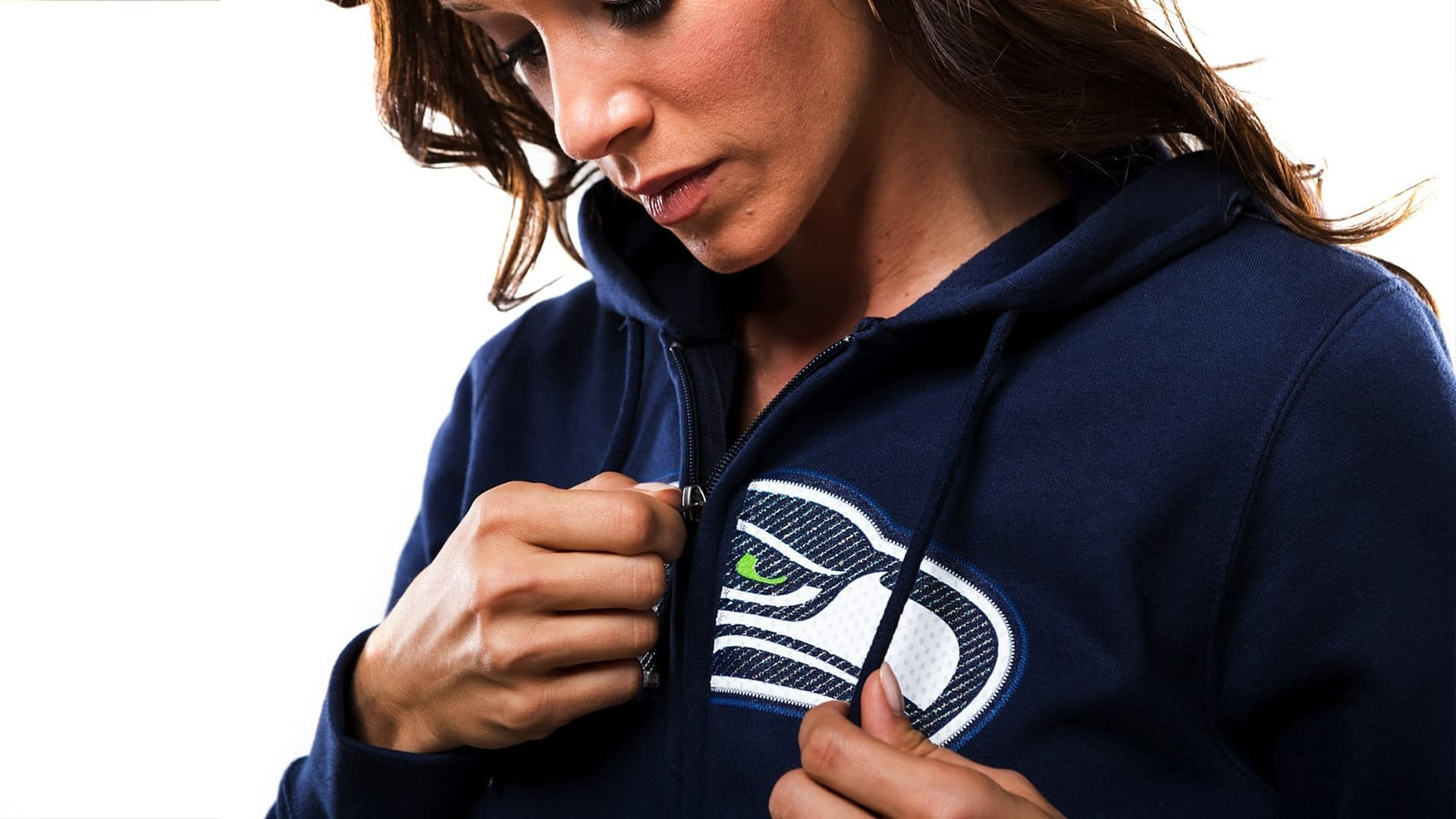 A woman modeling a Seahwaks sweater for Majestic, a sportswear manufacturer.