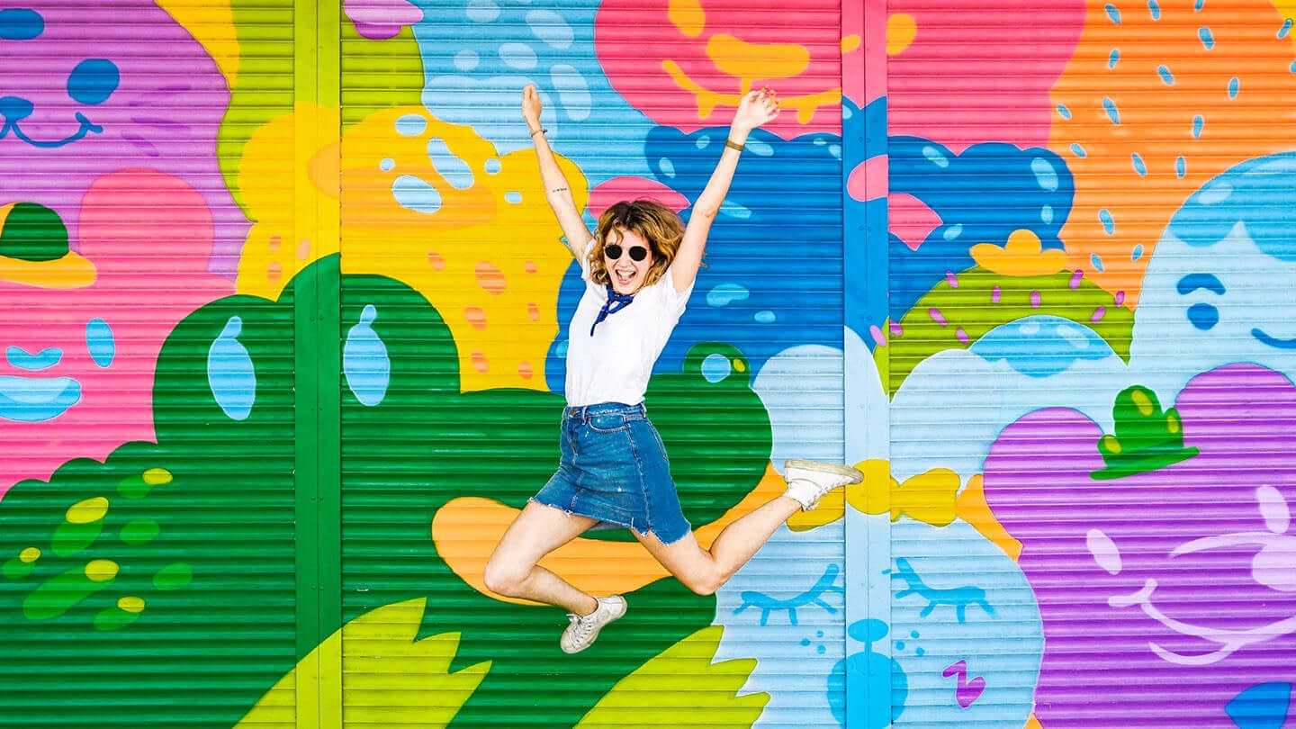 Girl jumping happily in front of a mural for our experience seekers integrated campaign