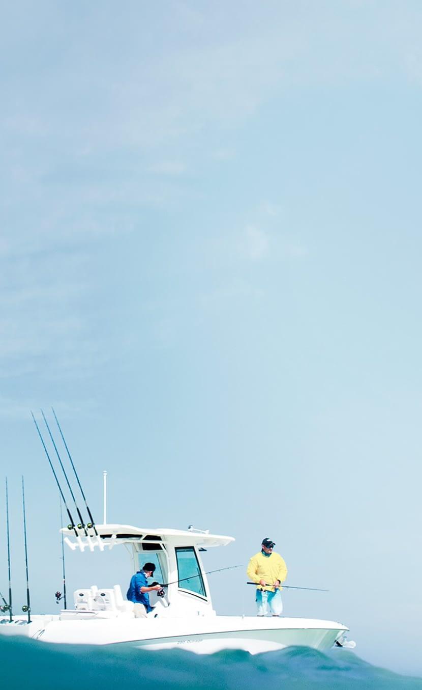 men fishing off side of boat in water
