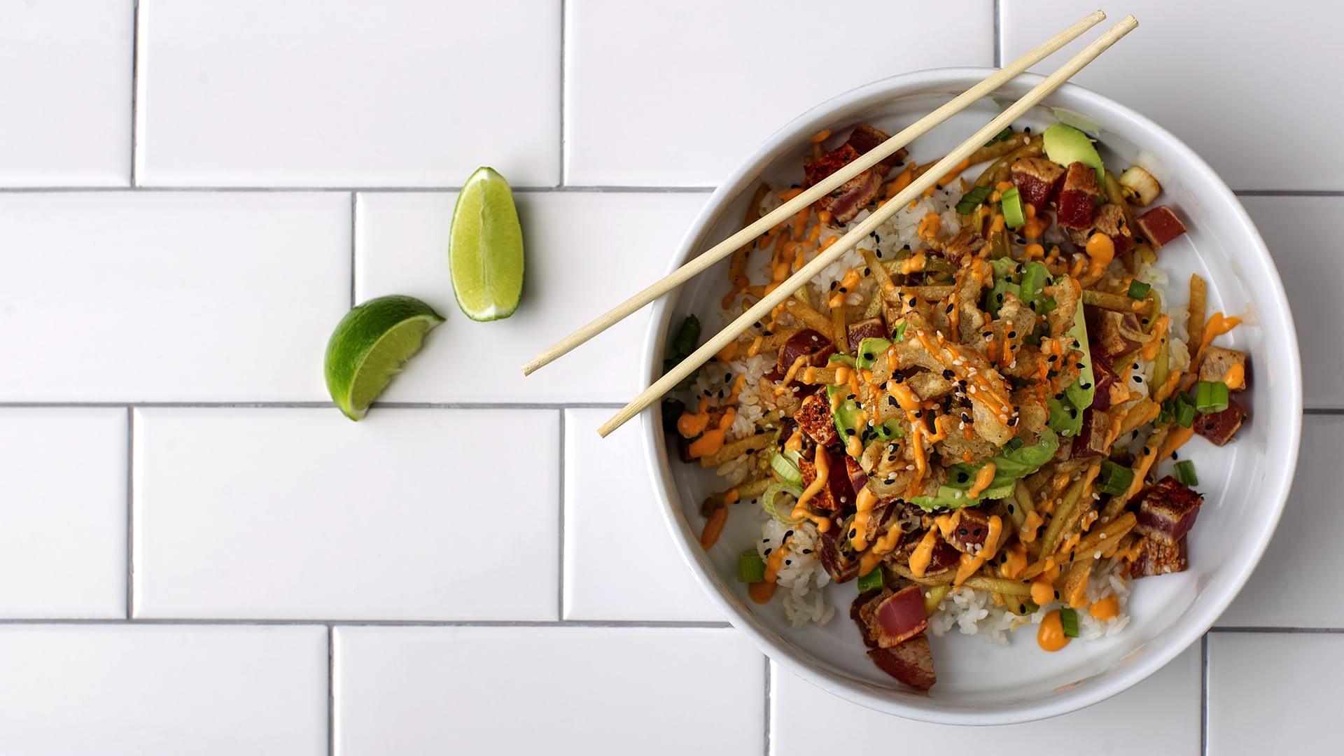 An overhead photo of a Ciccio Cali tuna bowl with chopsticks and a lime.