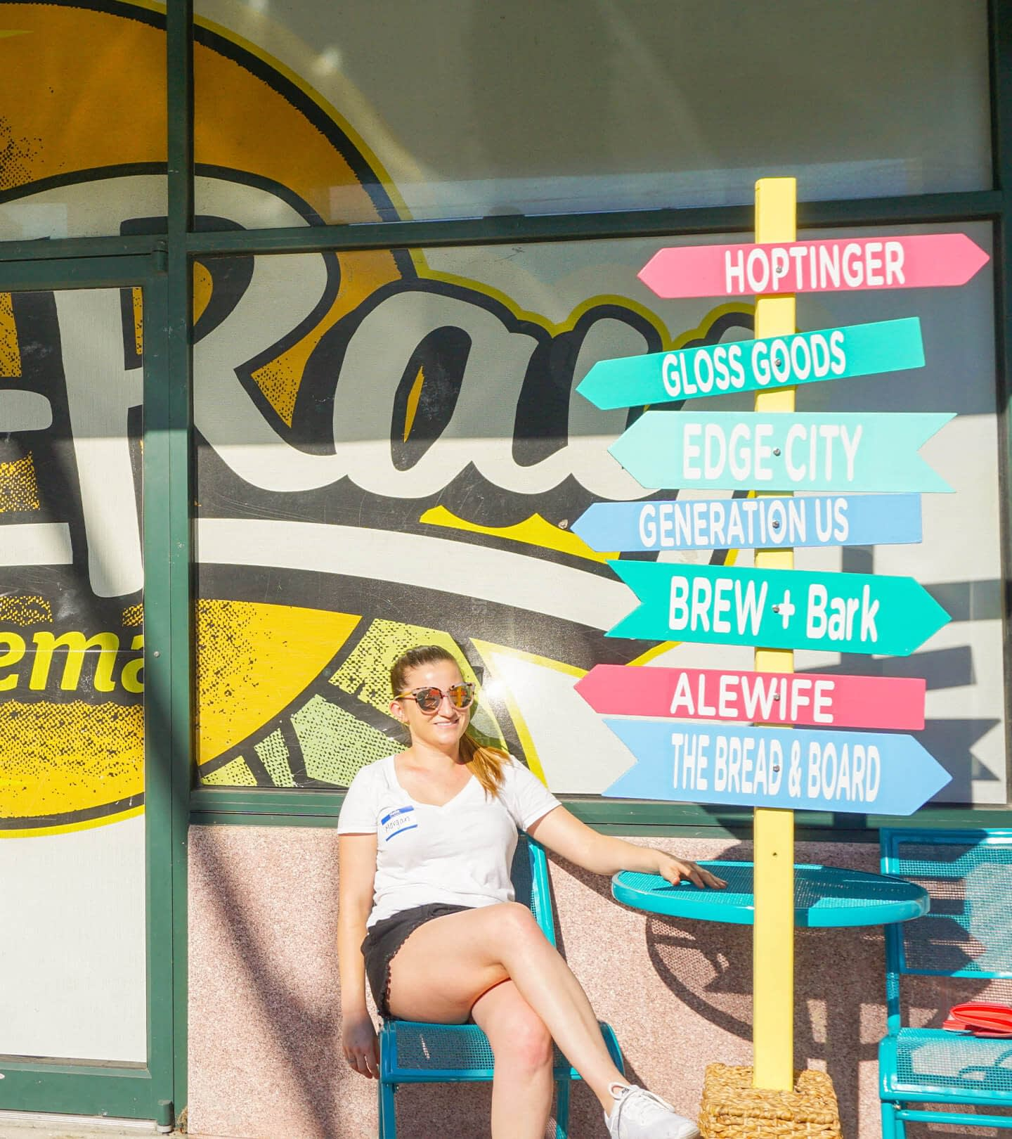 A girl sitting in the sun next to a wayfinding sign from our experience marketing component a Florida block party