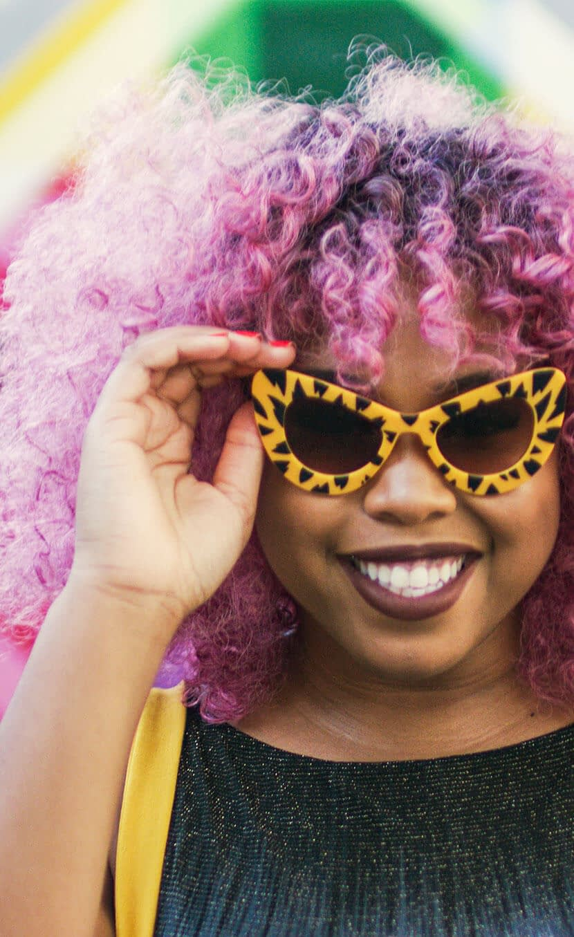 Woman with purple hair smiling wearing cheetah print glasses for our integrated campaign