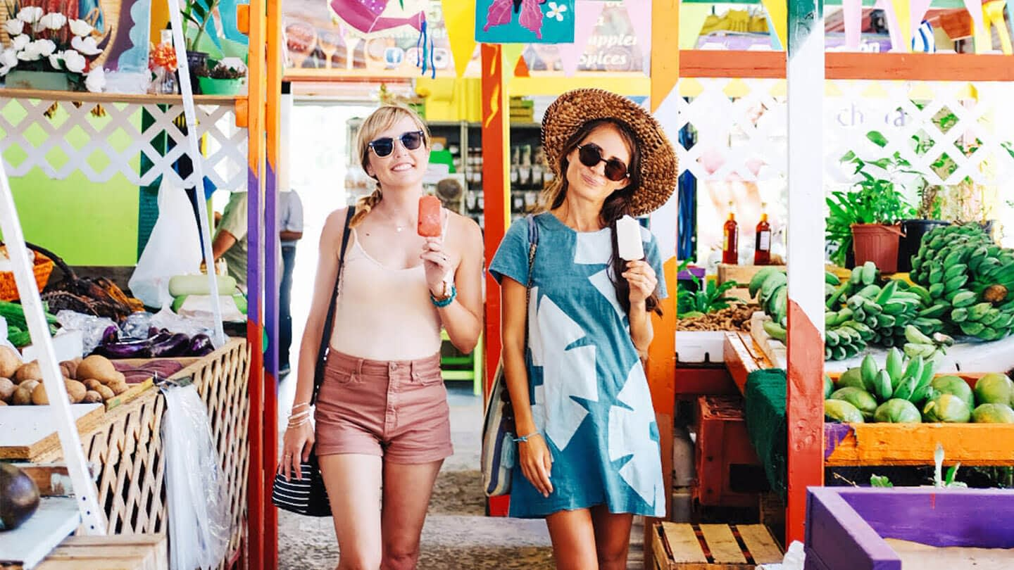 Two women standing at a local market in Miami for our experience seekers integrated campaign