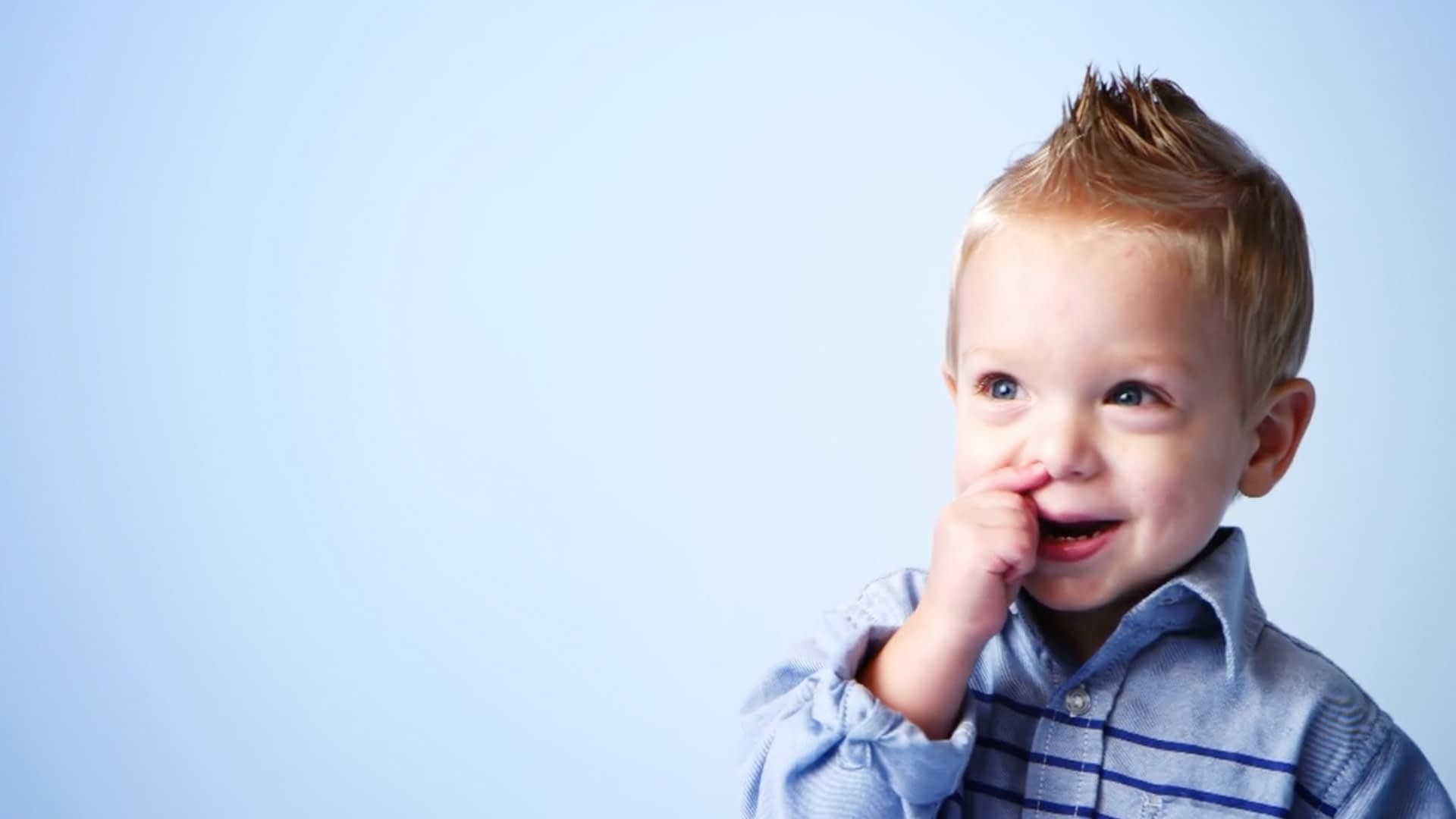 A little boy with a blonde mohawk laughing while picking his nose.