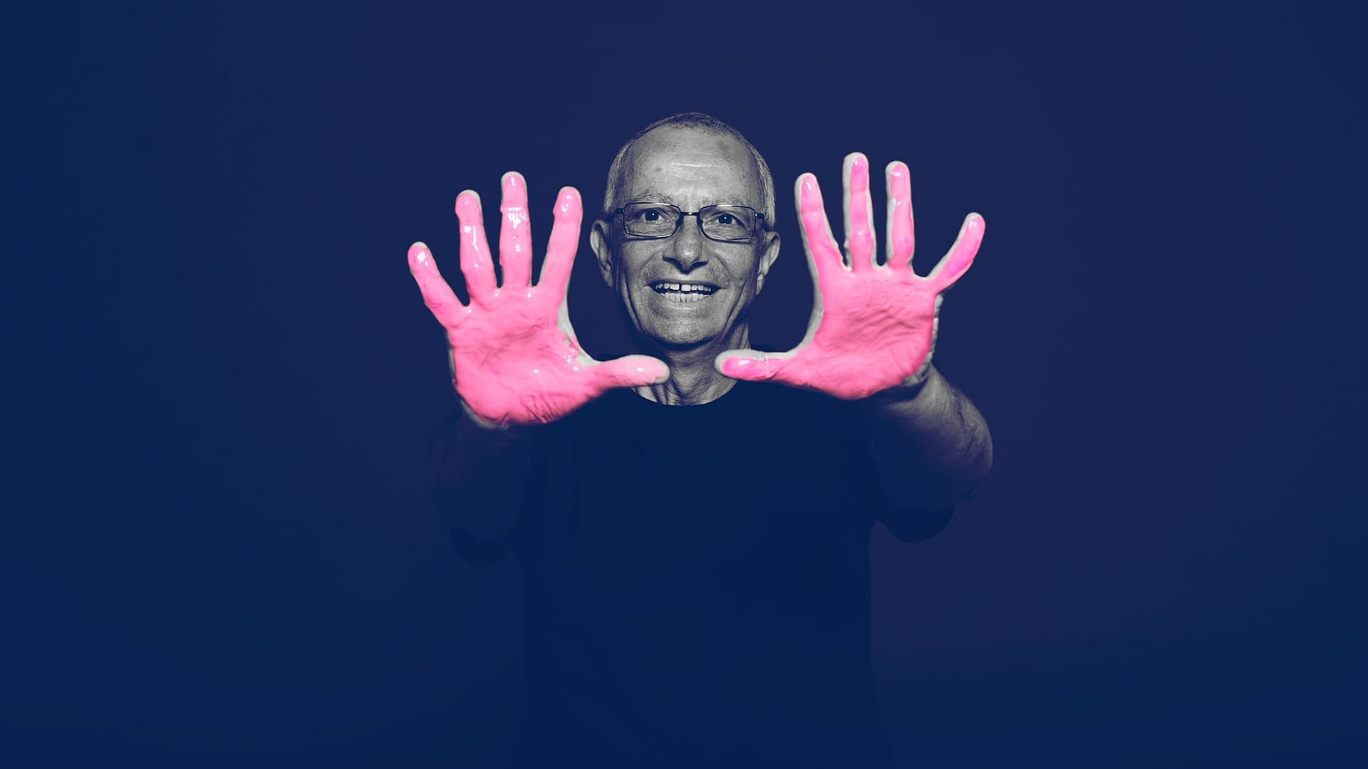 BayCare survivor posing for the in our hands campaign with pink paint on his hands