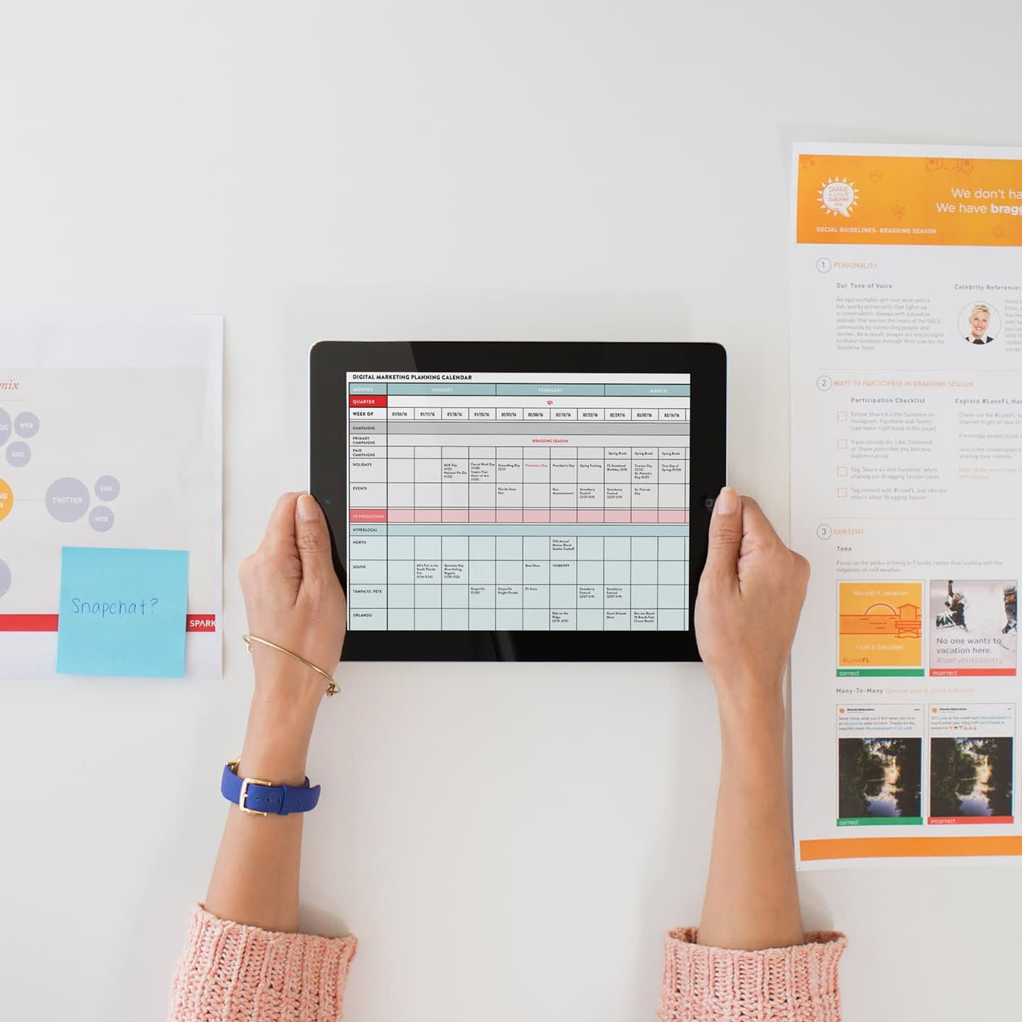 A woman holding out an iPad that displays a report with other papers on her desk.